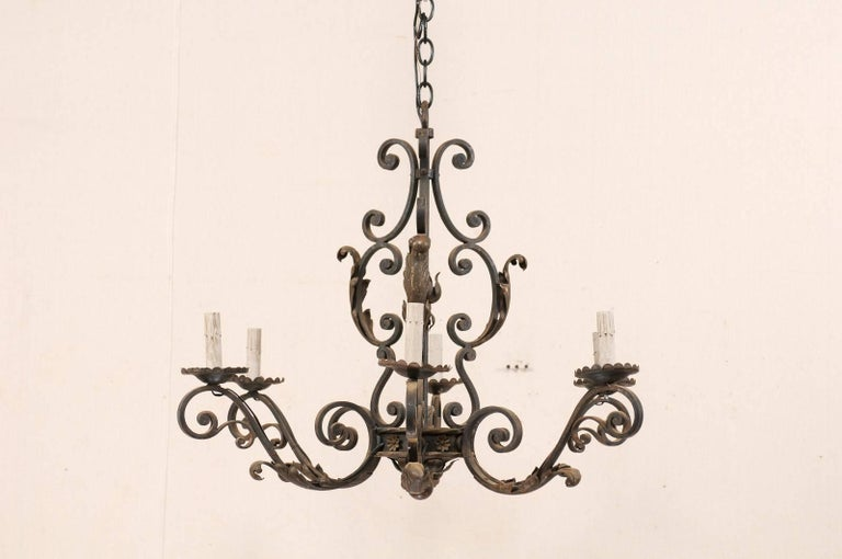 A French iron six-light chandelier from the mid-20th century. The armature of this vintage French chandelier is comprised of a series of C-scroll and S-scrolled forged iron motifs, decorated with acanthus leaves and small flowers. Each of the six