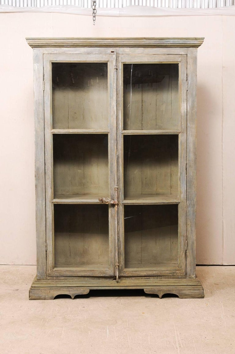 A tall display cabinet of 19th century French windows and reclaimed wood. This tall custom-made cabinet is comprised of two doors made from 19th century French windows, and a body of reclaimed and painted wood. This cabinet has substantial metal