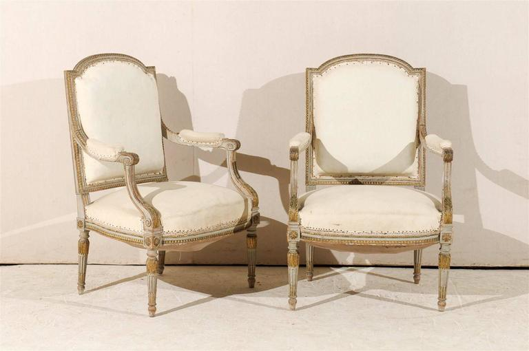 A pair of elegant French 19th century Louis XVI style fauteuils or armchairs with original paint, scrolled arms, fluted and tapered legs, gilded accents and Rosettes on the knees. Ready to be reupholstered. This pair would add a touch of beauty to