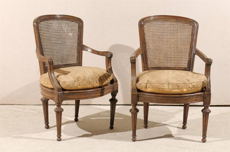 A pair of 18th century Italian wooden armchairs with cane seats and backs, tapered legs, scrolled arms and cushions.