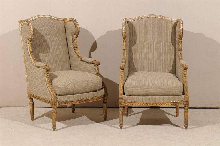 A pair of 19th century French Louis XVI style wingback chairs with good early paint, traces of gilding and nicely carved frame, including rosettes on the knees and guilloche frieze on the skirt. Fluted legs.