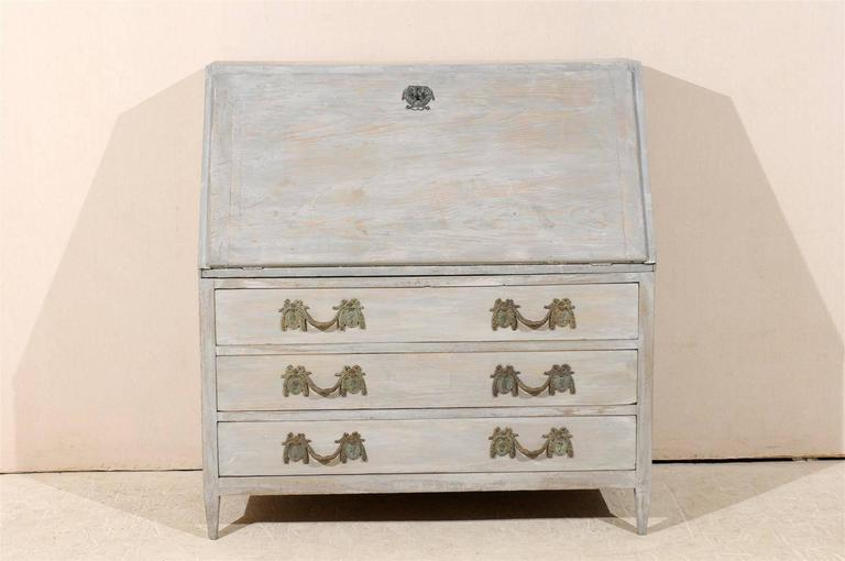 A Swedish mid-19th century painted wood Gustavian style slant-front desk or secretary with three lower drawers standing on short tapered feet.  Here are the measurements: 48