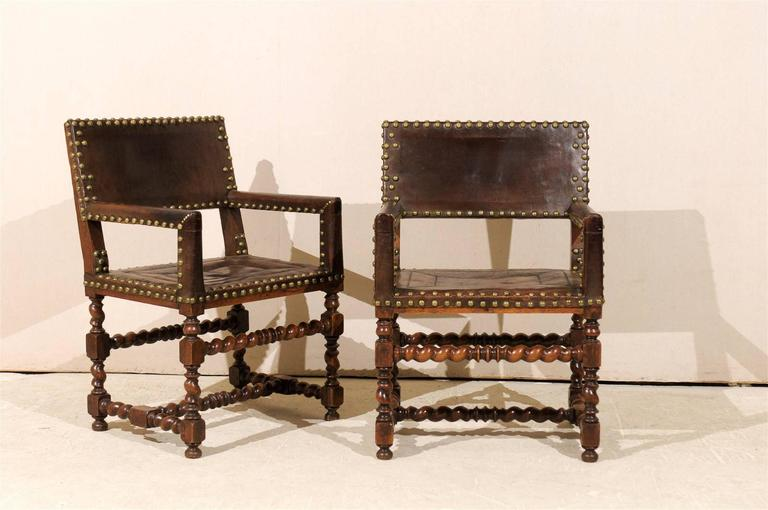 A pair of French 1920s wood and leather armchairs with repeating large round nail-heads along the trim, turned legs and barley-twist stretchers. This pair of beautifully warn early 20th century French armchairs would look perfect in a library, den