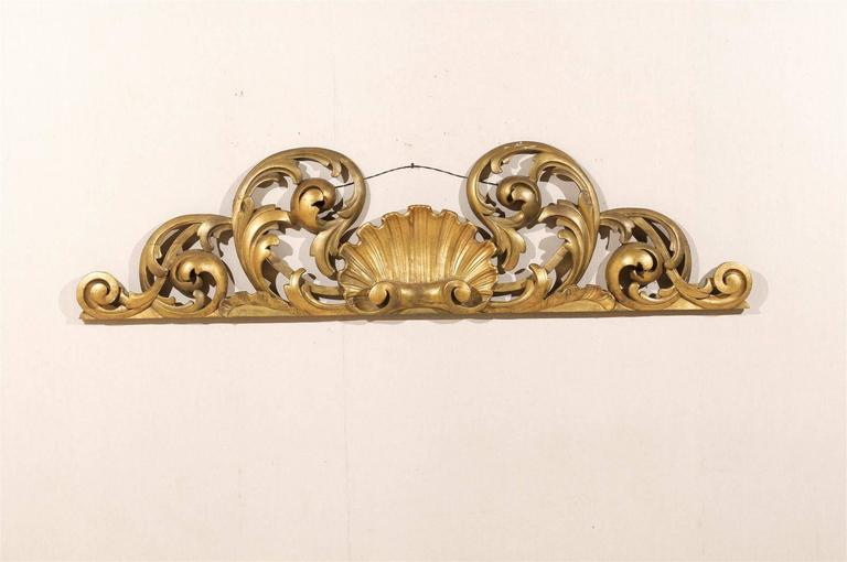 An Italian hand-carved and gilded wood wall decoration with Rinceaux motifs and central shell from the early 20th century.