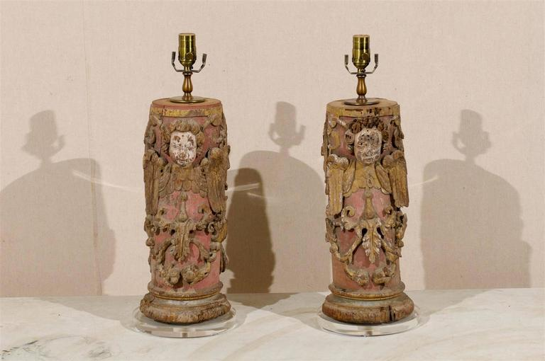 A pair of 18th century Portuguese painted red wood column table lamps with traces of gilding throughout.  These Southern European table lamps feature a wrap-around depiction that includes: carved angels, ornate scroll motifs and nicely carved