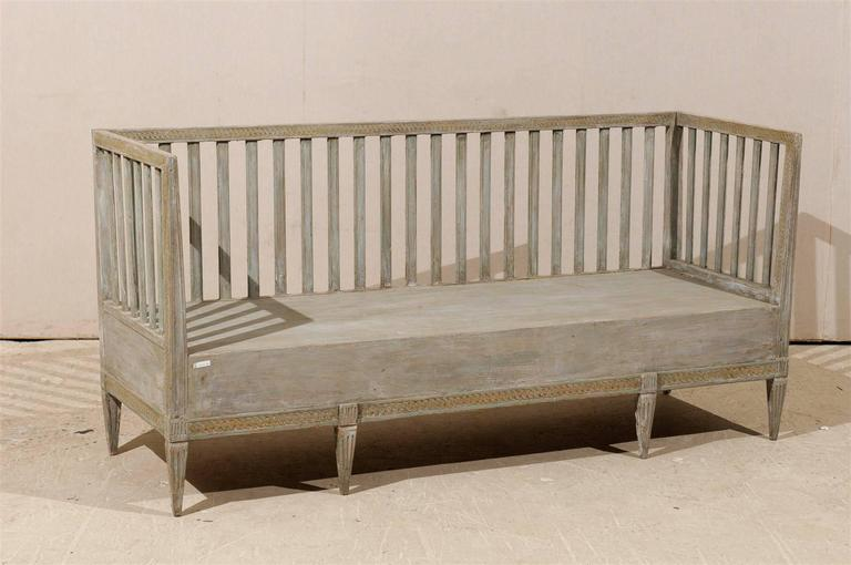 A Swedish period Gustavian late 18th-early 19th century period Gustavian painted wood bench with regular succession of slats, carved lower and upper rail and tapered legs.