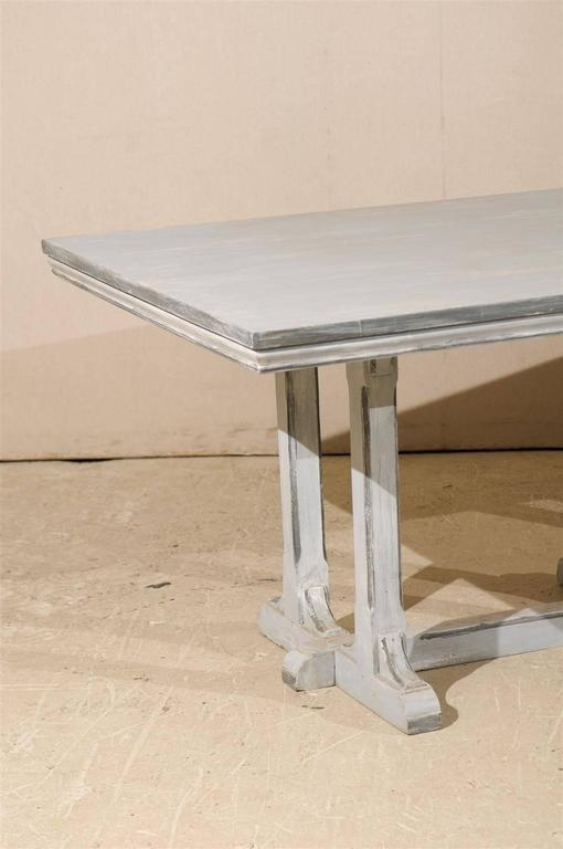 A large European grey painted wood rectangular dining table. This dining table features an old trestle base with cross stretcher supporting a later top. The edges have been highlighted with darker grey accents, providing more visual depth, 20th