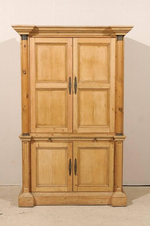 An exquisite tall English natural wood vintage cabinet. This tall cabinet with very linear profile features two hideaway doors at the top flanked with Doric style columns over two lower doors with flat pilasters. The top doors open up to adjustable