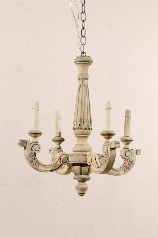 A French four-light painted and carved wood chandelier with thin central column and C-scrolled arms ornate with discreet leaf motif and terminated by a geometrical volute. From the mid-20th century, this French chandelier has been rewired for the US