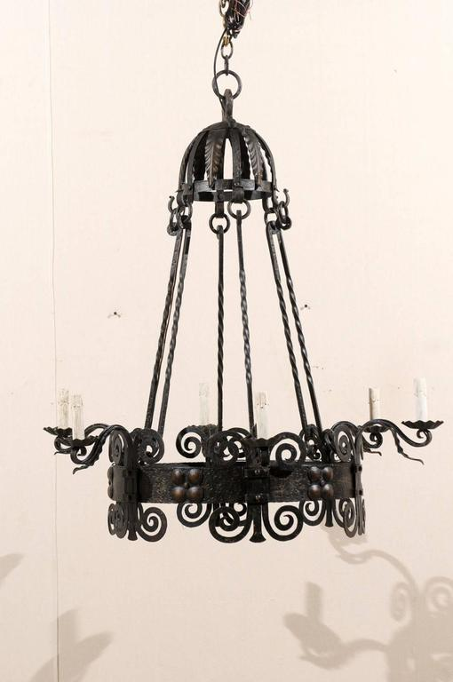 An Italian six-light black iron vintage chandelier. This mid-20th century Italian chandelier features scrolled motifs on the central circular ring with a raised, dotted flower design between each arm. This chandelier has the repeated scroll pattern