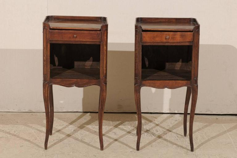 A pair of French 19th century side tables or nightstands. This pair of French stained wood bedside or side tables features a top drawer over an open lower shelf. The finish on the body is close to a Cabernet mahogany in color. The tabletop has