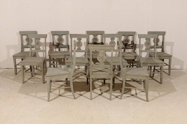 A set of 12 early 20th century carved wood side or dining chairs. Each of these chairs is adorned with an ionic column variation motif splat carving. Each of these column motifs also features nicely carved leaf images. These chairs have been made