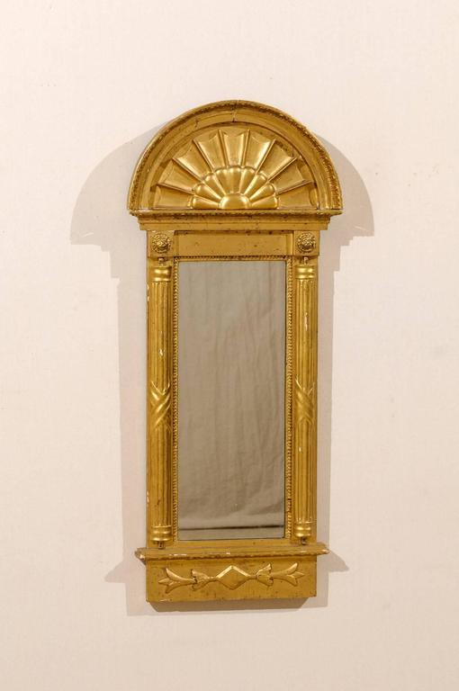 An early 19th century Swedish gilded mirror, circa 1820. This mirror features an arched crest and flanking fluted half columns. There are two lion carvings above each column. Within the arch there is a decoration reminiscent of a flower or a
