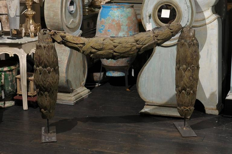 A Swedish 18th century large tole architectural swag mounted on an iron stand. This antique swag came from a building in Sweden. This unique piece consists of a rich foliage motif that appears to be draping on its stand. The general color of this