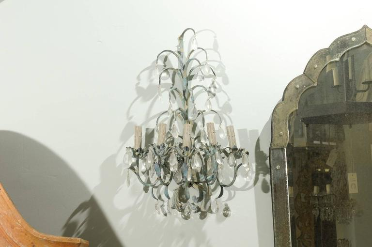 A pair of whimsical metal and crystal sconces. These French vintage sconces have five lights each. Each of these lights is supported by a sprouting foliage inspired bobèches. The upper part of these sconces has leaf-like over-hanging decorations