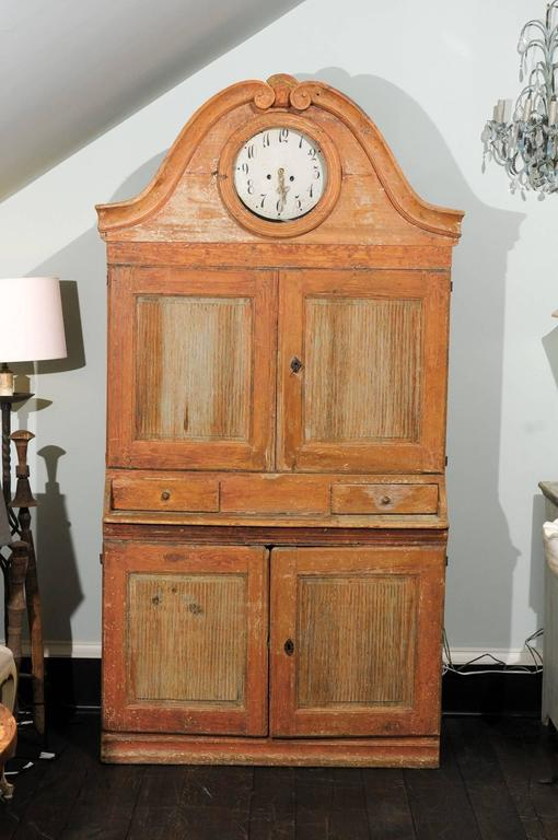This unique Swedish clock cabinet of the Karl Johan period from circa 1820 is much more than just a timepiece. With two drawers and shelves hidden behind four reeded doors and its original yam colored paint, this cabinet is perfect for a pantry, a