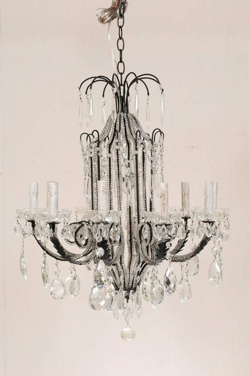 An Italian ten-light crystal and wrought iron chandelier. This Italian mid-20th century chandelier of black wrought iron is outlined along the body and arms with Italian bead-like glass trim. There is a crystal waterfall crown and hanging finial at
