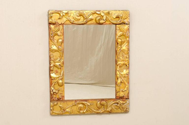 An Italian giltwood carved mirror made of 19th century fragments. This gilded rectangular Italian mirror is made of richly carved leafy scrolls decorating the frame. The surround is gesso over gilded wood, gold with spots of reddish ochre, nice age