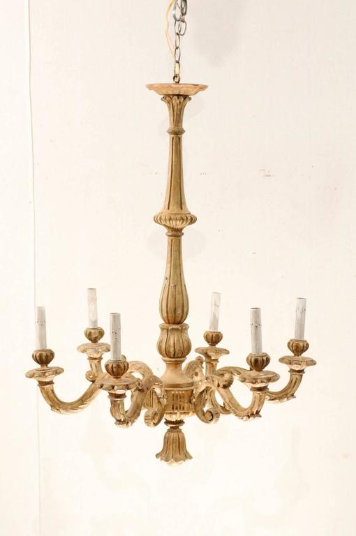An Italian early 20th century six-light nicely carved wooden chandelier. This tall Italian chandelier features a long and slender central column. Six s-scrolled arms flow from the bottom of the central column, leading outwards towards its candle