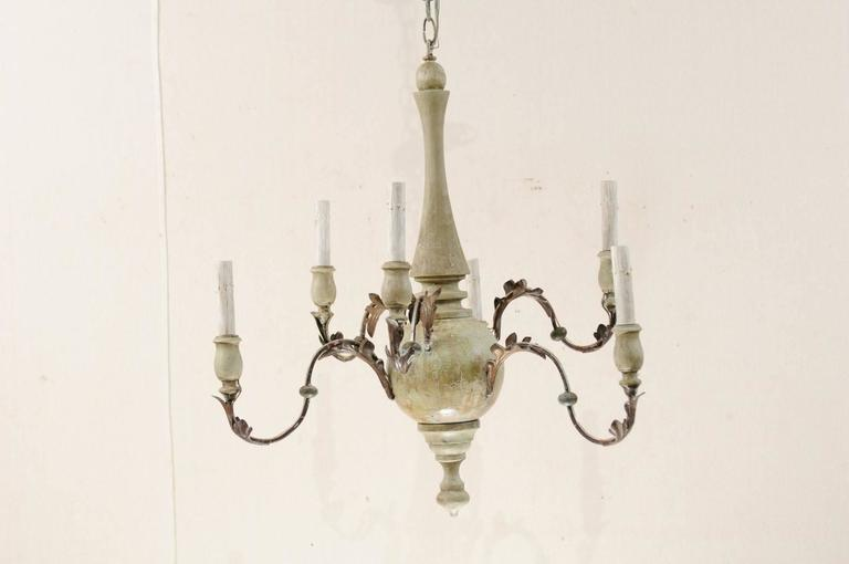 An Italian six-light painted wood and metal chandelier. This graceful mid-20th century Italian chandelier features a carved and painted wood column with metal swag arms extending out, at oscillating heights, from it's bulbous shaped centre. Each arm