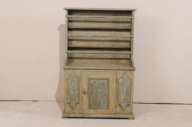 An early 19th century, Swedish painted wood cabinet with plate rack. This period Gustavian Swedish cabinet from the early 19th century features a plate rack top over cabinet bottom with one centered door. The cabinet is accented with a square shaped