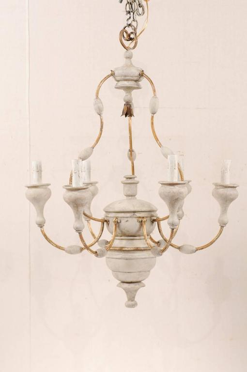 An Italian six-light painted wood and metal chandelier. This good sized mid-20th century Italian chandelier features a carved and painted wood column with metal swag arms extending out from the centre. Each arm metal arm features an oblong bead