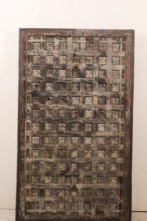 A 19th century wood carved Southern Indian decorative ceiling panel. This rectangular shaped wooden ceiling panel from the Tamil Nadu area features a depiction of delicately carved lotus flowers with the numerous coffered sections. This panel is