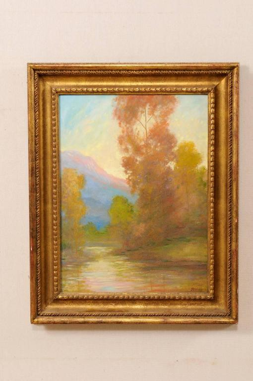 A David Sterling, American artist (1887-1971) landscape oil painting in frame. This is a romantic depiction of a water source surrounded by autumn trees and mountain in the distance. This painting is within a gold wood carved frame. Signed
