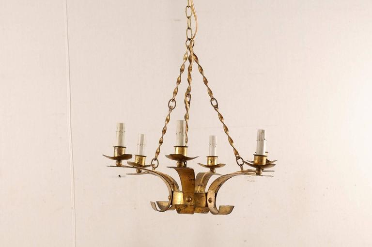A French mid-20th century six-light chandelier. This French chandelier has a modern design featuring a small circular centre with six arms rising up and out from the centre, each supporting their metal bobèches and painted candle sleeves at the top