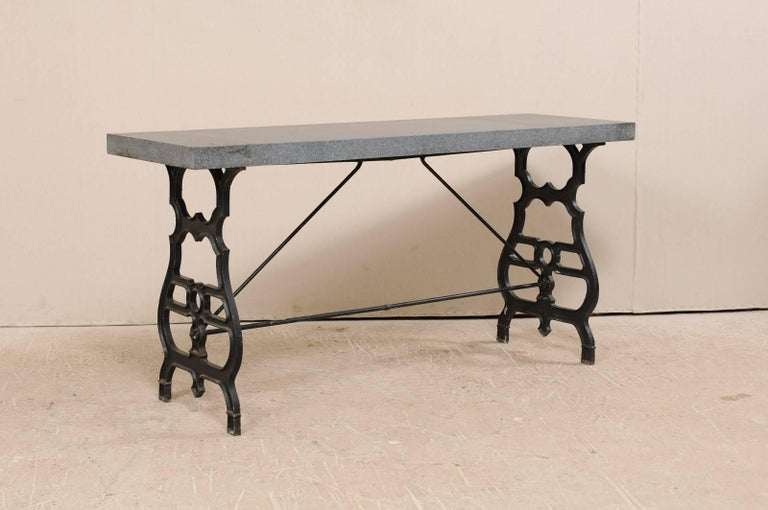 An antique French iron table with granite top. This French table, from the early 20th century, features a black iron base with a newer addition of a gray colored honed granite top. The base consists to two thin profiled sides, ornately forged and