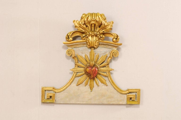 An 18th century Spanish carved wooden wall plaque. This Spanish wall decoration features beautiful gilded three dimensional carvings depicting a scrolling acanthus leaf motif at it's crest, and a flamed heart bursting from rays at the plaque's