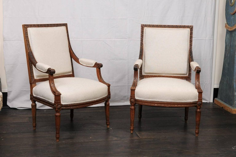 A pair of mid-20th century French Louis XVI style armchairs. This pair of French armchairs have beautiful, tightly carved details throughout which feature a repeating pattern of single flower and leaves about the chair back frame, scrolled knuckles