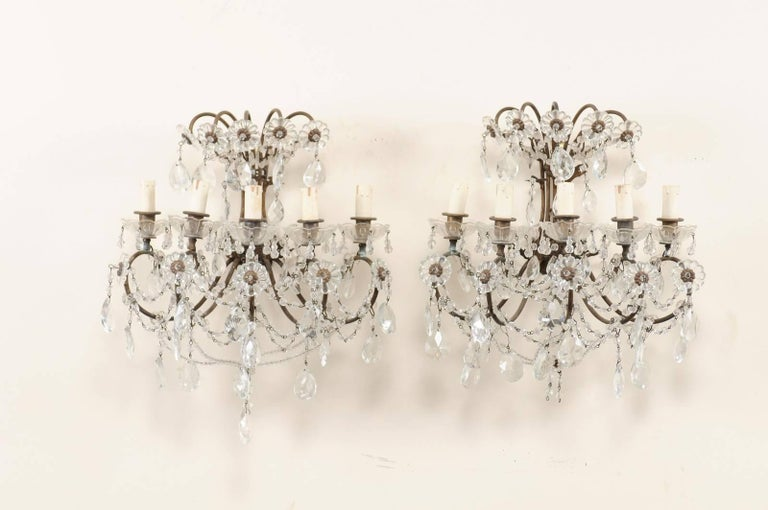 A pair of Italian crystal five-light sconces from the mid-20th century. This pair of Italian crystal sconces each feature five lights set within scrolling metal armature, adorn with delicately swagged crystals, beading and crystal flowers