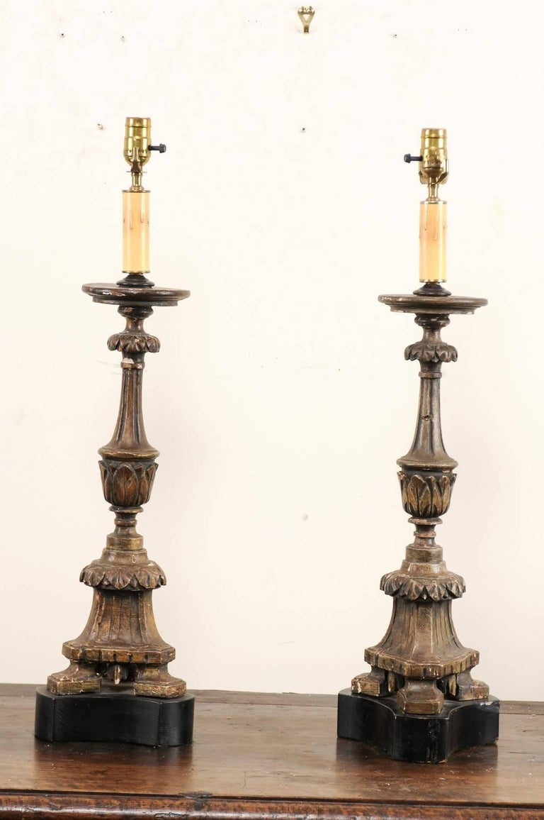 A pair of Italian 19th century carved wood altar sticks made into table lamps. This pair of Italian table lamps have been fashioned from antique carved wood altar sticks. The altar sticks have nice fluted details with a decorative leaf motif and