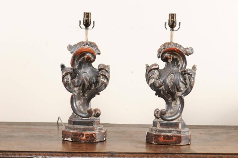 A pair of Italian altar table lamps from the early 20th century. This pair of table lamps have been fashioned from antique Rococo style, hand-carved Italian fragment pieces. These lamps have beautifully fluid shapes with scrolls and acanthus leaves