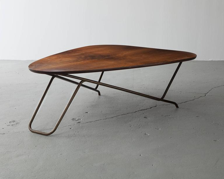 Wood coffee table with California walnut veneer and a sculptural brass base. This design is commonly referred to as the