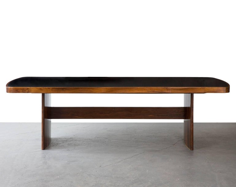 Soft-edged rectangular dining table in jacaranda with black under painted glass top and curved legs. Designed by Joaquim Tenreiro, Brazil, circa 1949.