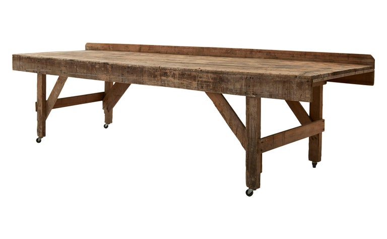 Made in America in the early 20th century, our industrial Vintage Work Table is crafted from patinaed wood, with caster wheels on all four legs. Although well-worn in appearance with many scratches and markings consistent with its age and use, this