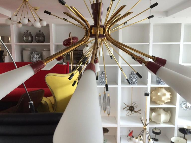 A graceful eight-arm or eight-light chandelier with brass tubular arms, distinctive red enameled details and handblown opaline glass open shades which can be directed down (as shown) or up.