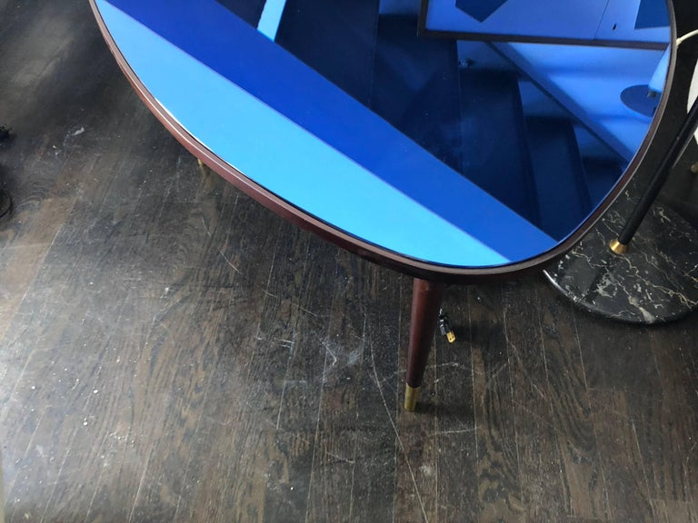 Beautifully carved tri-sided mahogany coffee table resting on three mahogany legs with brass caps and topped by original cobalt mirror (inset). Designed by Osvaldo Borsani and manufactured in Italy in the early to mid-1960s. All original.