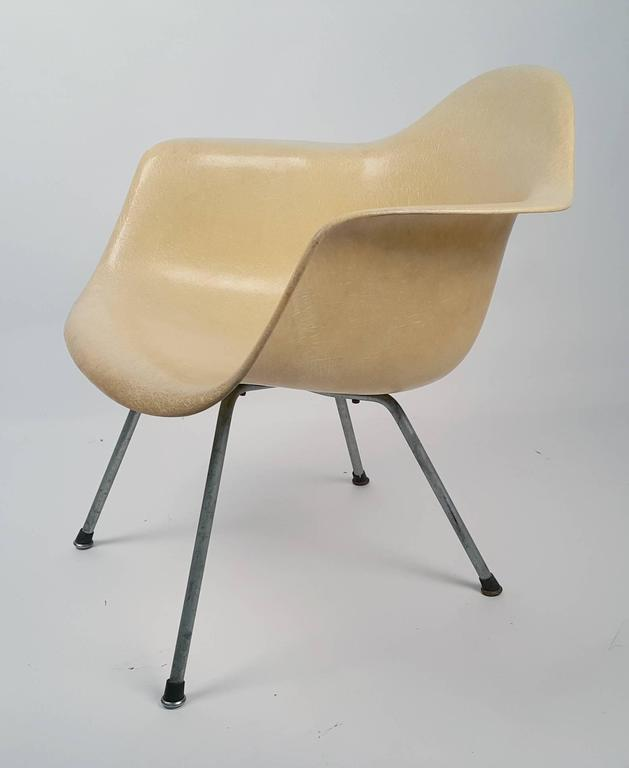 Charles and Ray Eames designed low lounge armshell with X-base. Original zinc base, original screws, Original boot glides. Early transitional parchment fiberglass shell with large shock mounts from the Venice Office.