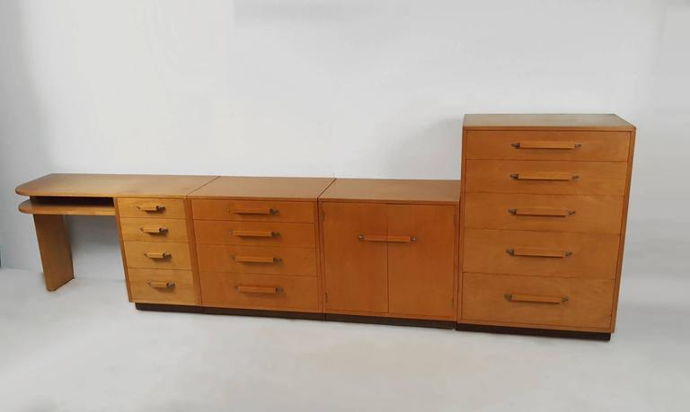 A collection of five different components from the 'Flexible Home Arrangement' collection designed by architect Eliel Saarinen in collaboration with his daughter for Johnson Furniture Company. Includes a desk, two chests of drawers, a cabinet with