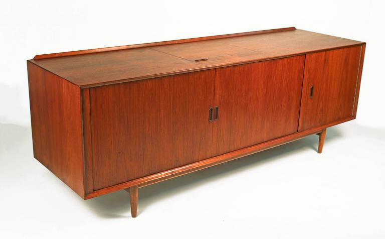 Teak wood Scandinavian Modern stereo or media cabinet. The unit consists of two beautiful book-matched tambour doors and a flip-top hatch which was designed to provide easy turn table access. Many compartments for storage and stereo or television