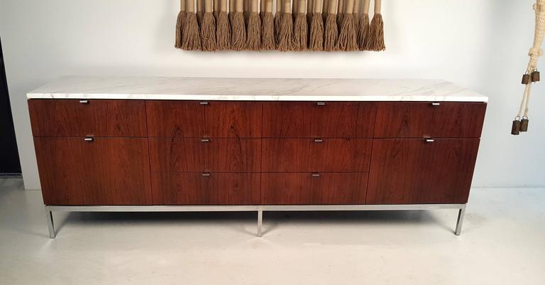 Ten-drawer Brazilian rosewood credenza with Carrara marble top designed by Florence Knoll for Knoll International. Chrome-plated base and hardware and oak interiors. Very good original condition.