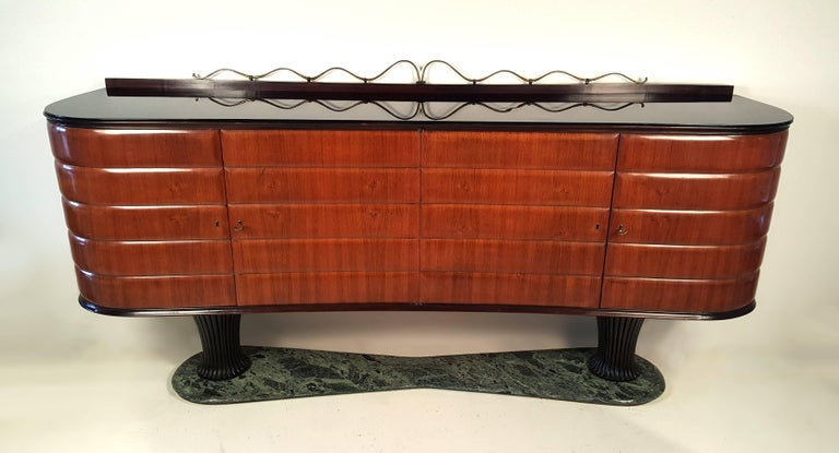 A phenomenal early Italian modernist server in sculpted Italian walnut with hand-carved mahogany bases, black milk glass top, hand-forged solid brass ornamentation and verde marble base with brushed brass reveal. An elegant and functional piece of