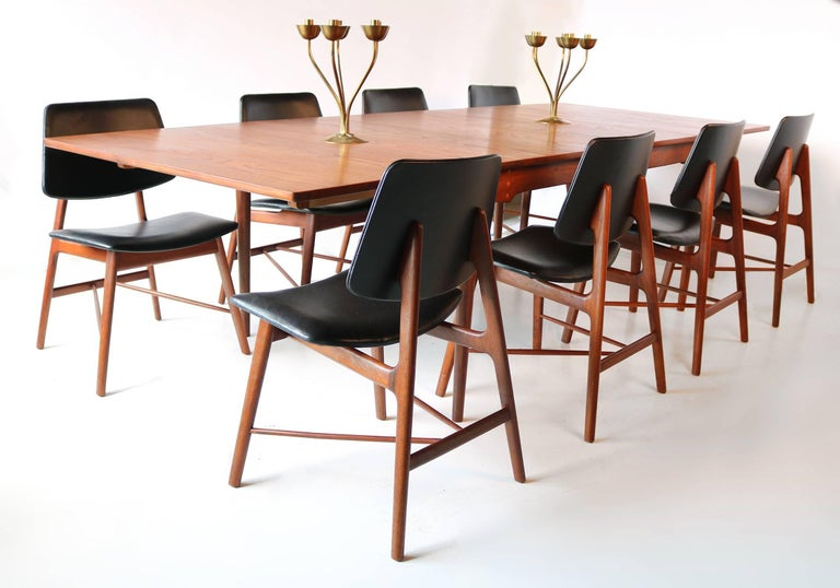 Set of eight Finn Juhl solid teak sculptural dining chairs recovered in a smooth oiled black leather and completely refinished in a waxed teak oil finish. The table measures 43w x 62L x 29
