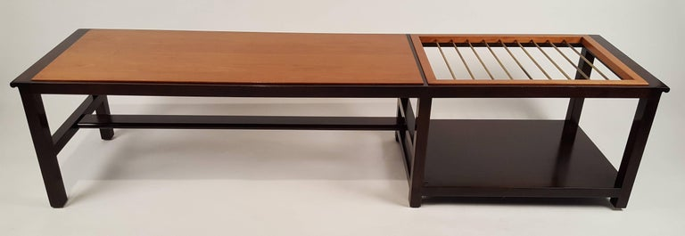 An exceptional Dunbar coffee table or bench (Model 5933a) with built-in brass rods for suspending magazines. Another option would be to recess a glass top over the rods to use as a surface for beverages. The rim and base are constructed of solid