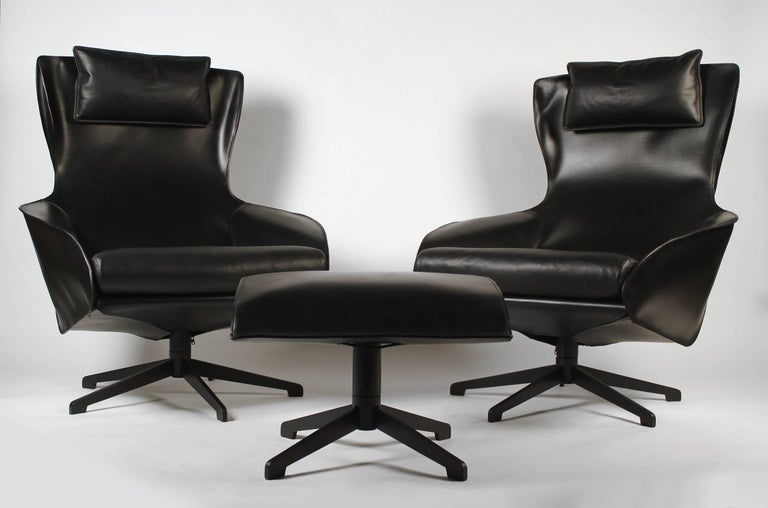 This pair of Mario Bellini model 423 cab lounge chairs are in excellent shape and only show the slightest amount of wear. They look practically brand new. The stitched black leather upholstery with the down-filled pillow gives these chairs a unique