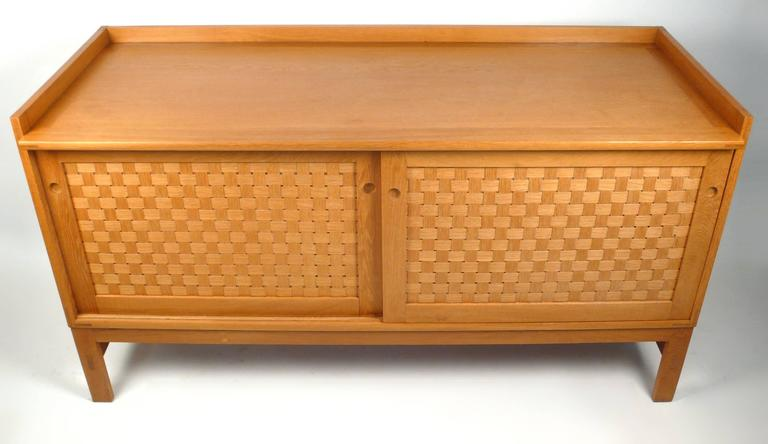 A fine and rare Danish modern oak sideboard designed by Ilse Rix for Uldum Møbelfabrik. This piece is generously proportioned and the woven front sliding doors open to reveal a series of finger jointed sliding drawers, some of which are lined in