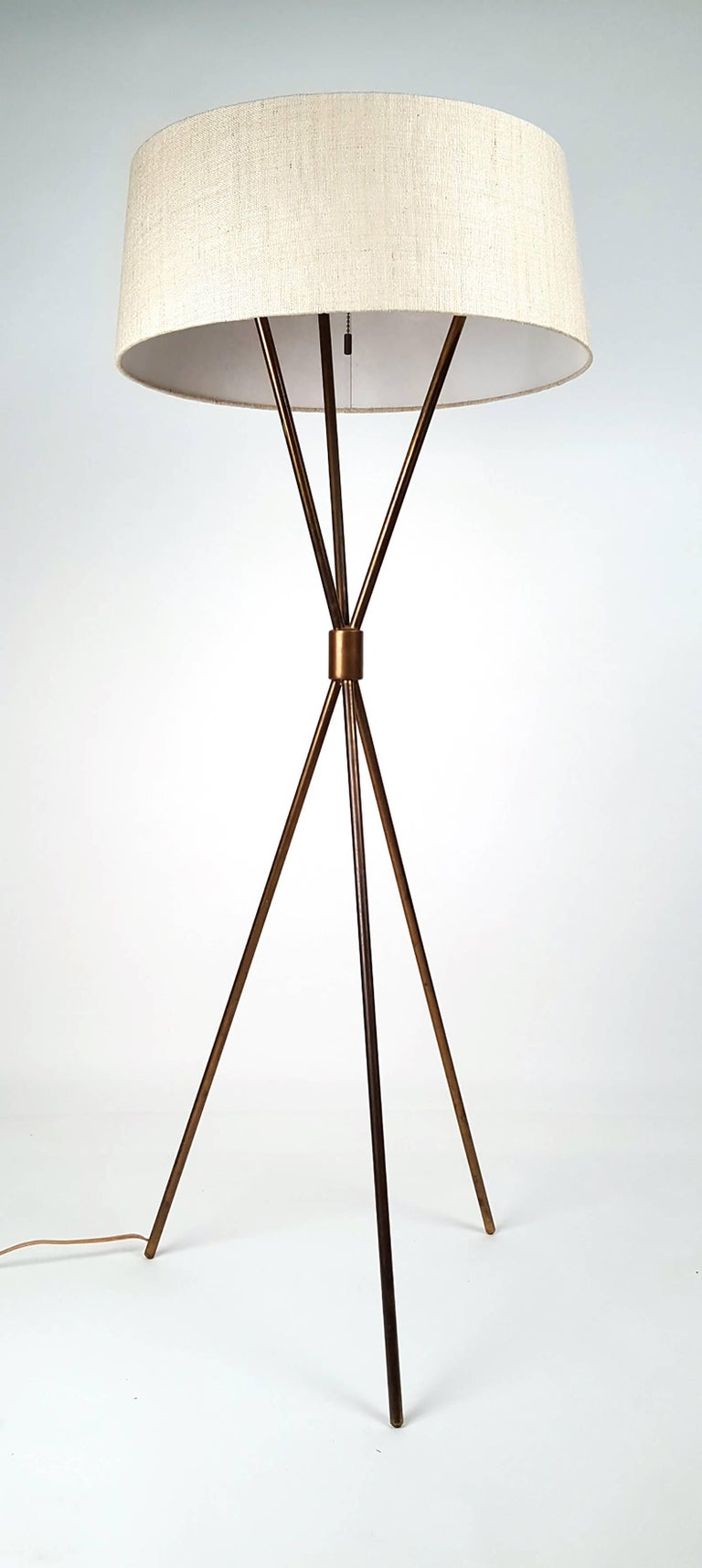 Early 1950s brass tripod floor lamp by T.H. Robsjohn-Gibbings for Hansen. Distributed by Widdicomb Furniture Company. Model #201-M. Exceptional patina. Beautiful shade. Functions as intended.